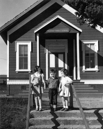 1950 black and white photo of Murray School House with 3 kids at front step