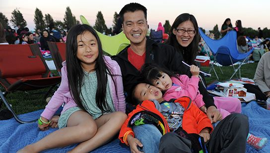 A family on the lawn at PicnicFlix movie night